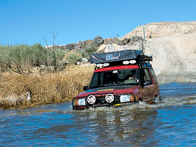 03084w 14z+Land Rover NAS 110 Defender+Front Driver Side View Cars Over River