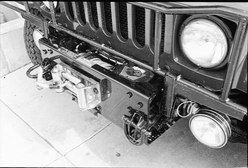 Another option on civilian models is a 12,000-pound Warn electric winch mounted in a cradle that doesn&#8217t reduce the approach angle as much as other winch mounts we&#8217ve seen. The tow loops on the front are standard and shared with the military trucks. A few military Hummers have winches, but they&#8217re specially made to military specs.