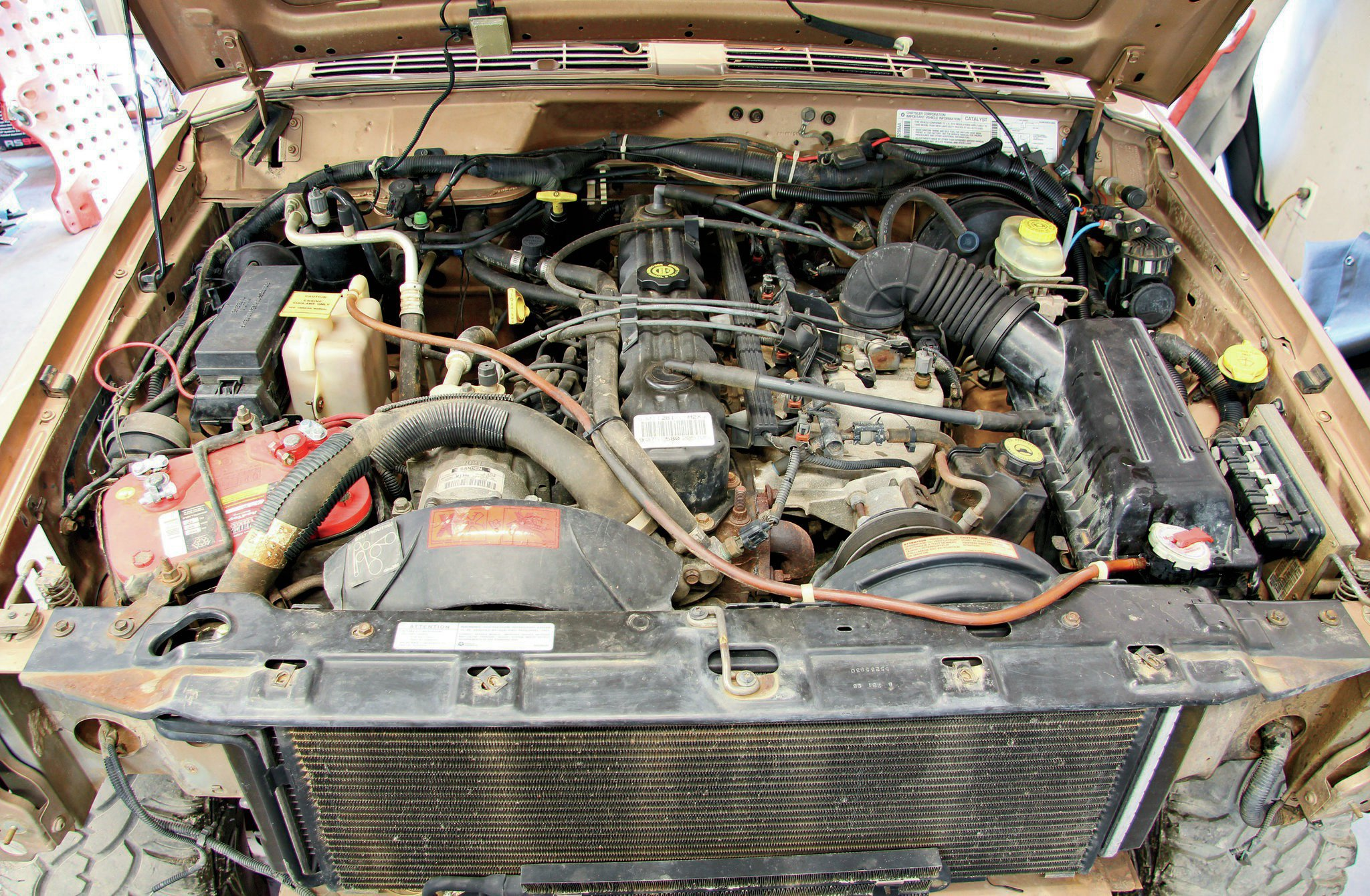 Under the hood rests the stock 4.0L inline-six engine. The Optima RedTop battery has some age on it but is holding a charge fine. We noticed that the XJ had an all-too-common exhaust manifold crack, but that will be a problem we will address in another installment.