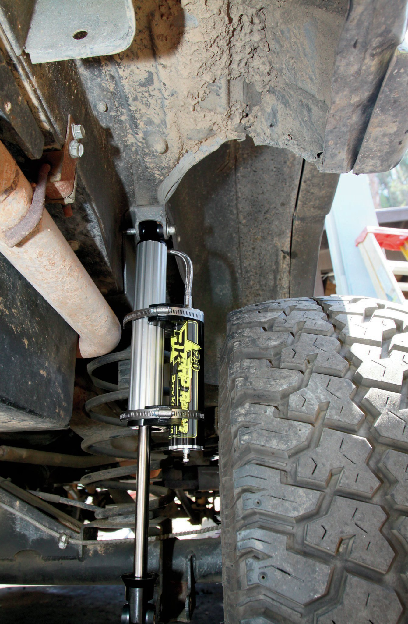 Like we said, it is a unique setup with the rear coil conversion. Rock Krawler had never built shocks for this application before, and as-delivered, the reservoirs were just too close to the tire for our liking. However, the Jeeps R Us crew figured it out in short order. The way the top bushing and reservoir line are oriented, by switching the shocks from side to side and then rotating the reservoirs so they sat behind the shocks, it all fit great. We've been in contact with Rock Krawler, and they know what we did, so future shocks coming out of the shop will already be set right for this application.