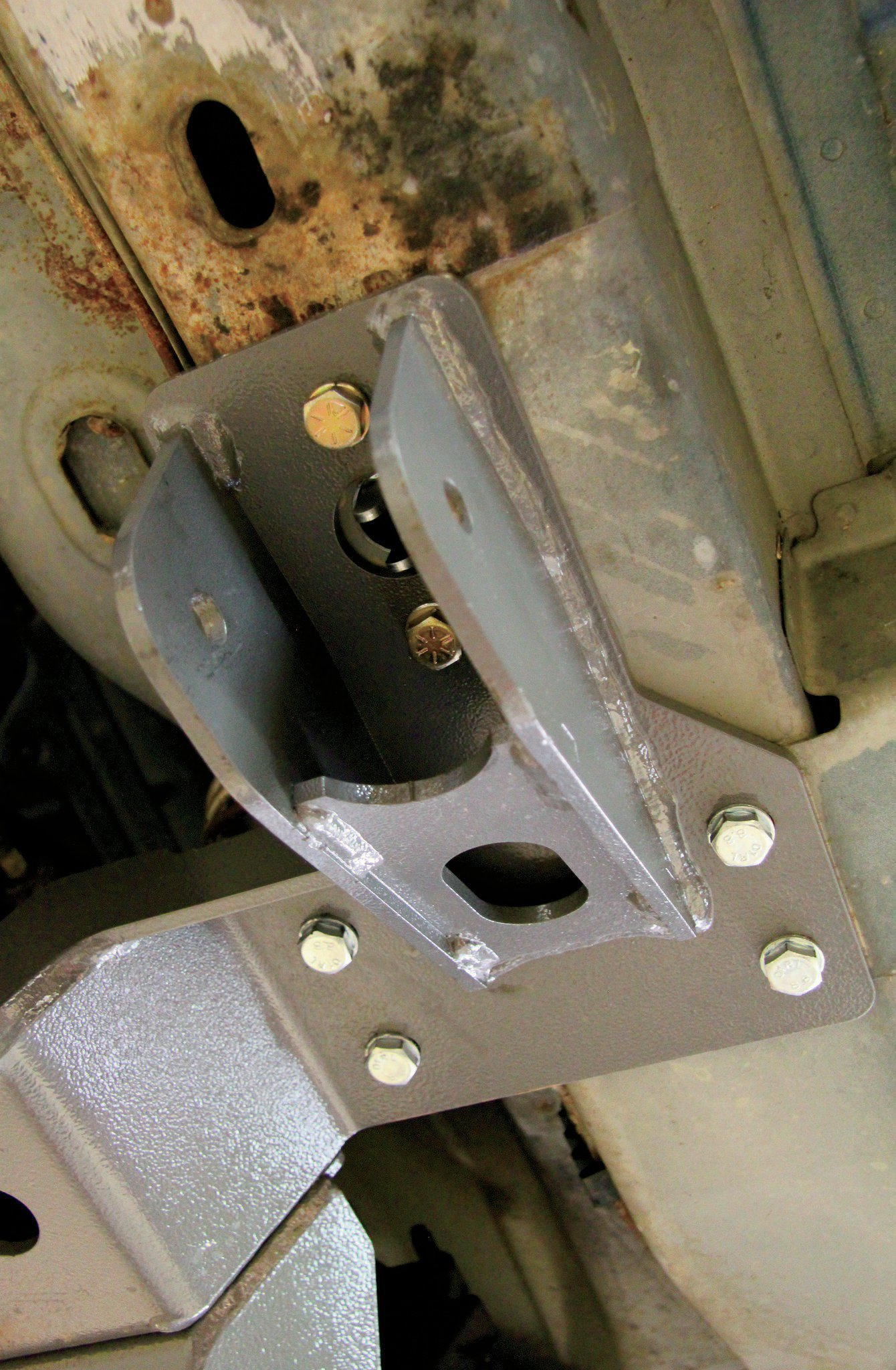 We started by installing the Rough Country long-arm suspension. The kit uses a 1⁄4-inch-thick replacement crossmember, which bolts directly to the four stock attachment points on each side of the Unitbody. To provide additional support, two extra bolts are secured above the control arm mounting location. Creating the opening for the flag nuts (nuts with tabs welded to them) will require either a 11⁄4-inch hole saw or a large unibit.