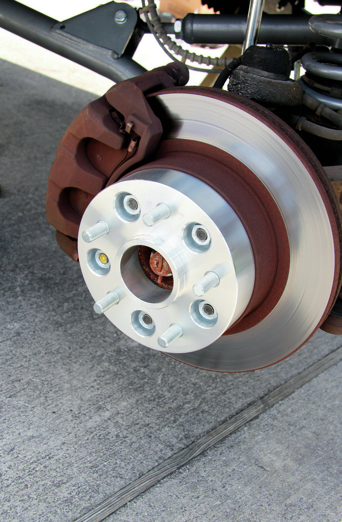 Since the long-arm suspension set us back more than we originally budgeted for, something had to go. In our case, it was aftermarket wheels. To allow us to re-use our factory 16-inch WJ wheels; we added at set of 1.5-inch wheel spacers to our Rough Country order. After dousing the studs in Loctite, we torqued the hub-centric spacers down.