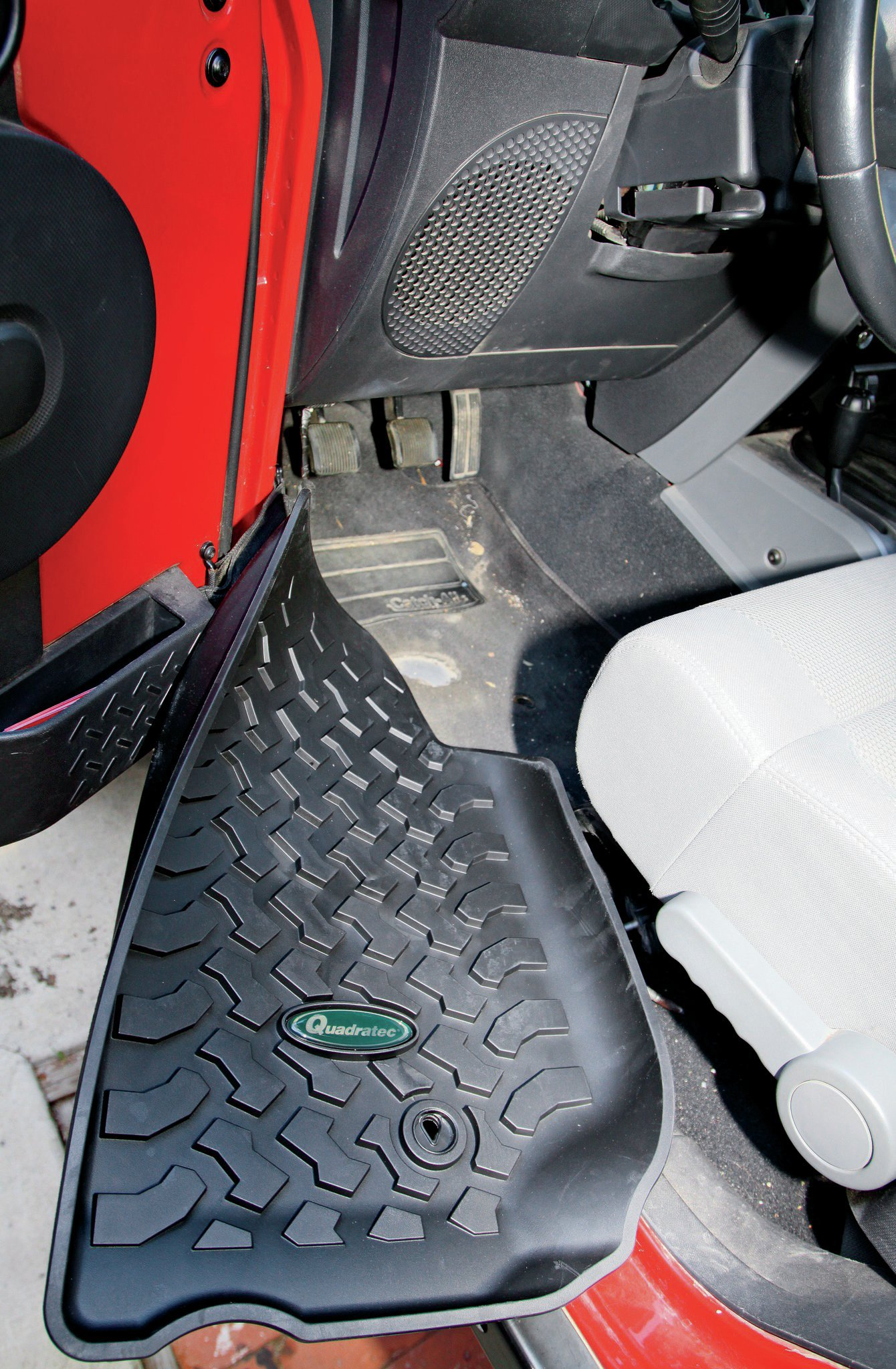 """One of the things that happened to our '07 Wrangler very early on (Cappa estimates it was before it even hit 30,000 miles) was that the front driver side floormat ended up with a hole completely worn through it. I can't help but wonder if the floormat just wasn't made with clutch-pedal use in mind. Hazel and I both thought that Cappa just wore through to the floorboards, but in fact, his solution was much better. Cappa duct taped a piece of aluminum to the back of the floor mat. That solved the issue but was way butch. So, I replaced that """"fix"""" with these floormats from Quadratec. Tested to over 100 degrees, these mats are also great for keeping mud, dirt, snow, and water from your carpet and after that, the floor of your Jeep."""