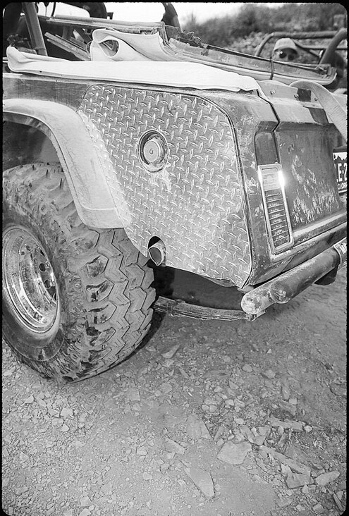The rear quarter-panel guard is made from diamond-plate aluminum. Holes were cut for the fuel filler and the exhaust, which exits through the lower part of the panel to avoid trail debris. The rear wheel openings were enlarged to accommodate Wrangler fender flares, and a 2-inch body lift was needed to fit the 35x14.50 Super Swamper SSR radials mounted on American Racing 15x10 chrome wheels. Also visible is the owner-built rear bumper.