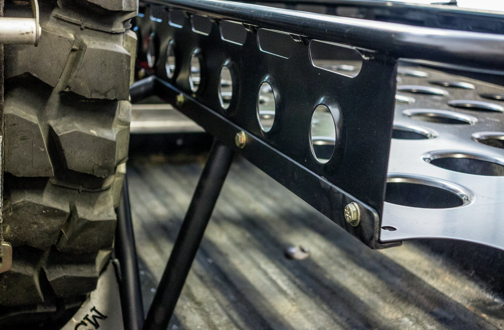The spare tire mount was built out of 1-inch tubing and acted as the foundation for the rail that holds the Baja Basket on the driver side. Note that the basket bolts into the mount and can easily be removed if necessary.