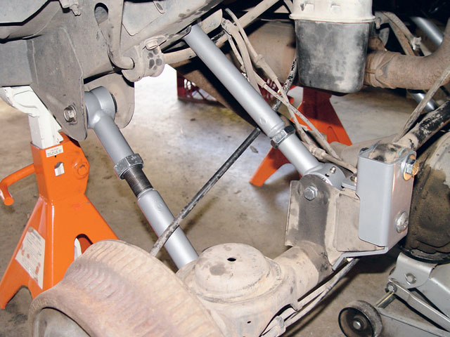 If you want control arms with Super-Flex joints and full adjustability for your Grand you'll need to upgrade to RE3715 (lowers), RE3783 (upper, rear), and RE3780 (upper, front) as we did. While it adds quite a bit to the kit cost, it allows you to fine tune the axle alignment (caster) and pinion angle to provide the least vibration and best U-joint durability. Rubicon Express specifies a rear lower arm length of 17.25 inches and 16.25 inches for the front, but you must still check your driveline angles and adjust accordingly. Remember to always install the arms with the rubber bushing in the unibody's frame mount and the Super-Flex joint in the axle bracket. Set the coil spring in its cup, jack the axle into posi