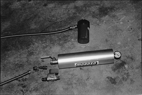 The system uses a sandwich adapter on the oil filter. Braided-stainless hose and aluminum AN fittings plumb the Accumulator into the oiling system. The Accumulator is essentially a reservoir with a floating piston. The floating piston allows the unit to be pressurized without causing the oil to foam. It holds three quarts and has a gauge that monitors the pressure.