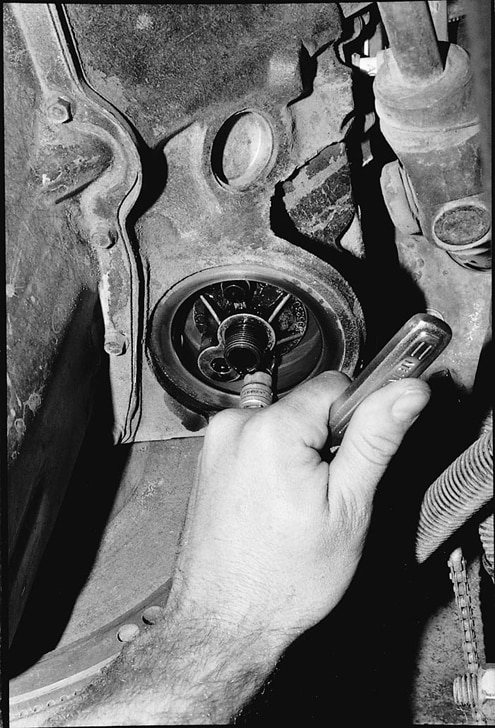 The oil-filter mount is unbolted from the block, and the area is cleaned with a rag. The new mount doesn&#8217t have a pressure bypass like the factory unit.