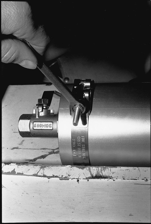 Install the Accumulator in the clamps and tighten securely. Be sure that the manual valve, gauge, and air-fill valve are accessible.