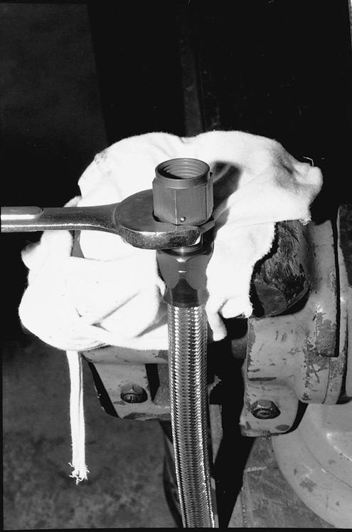 Here the fitting is protected with a rag and placed in a vise. The second part of the fitting is lubricated with engine oil, and the two pieces are threaded together. We mounted the hose and wiring inside the framerail for protection.