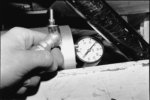 With the valve open, the Accumulator is pressurized to 60 psi with compressed air. This is done to move the floating piston to the empty position. The pressure is bled down to 6 psi and the engine is started. The Accumulator will fill up and build pressure.