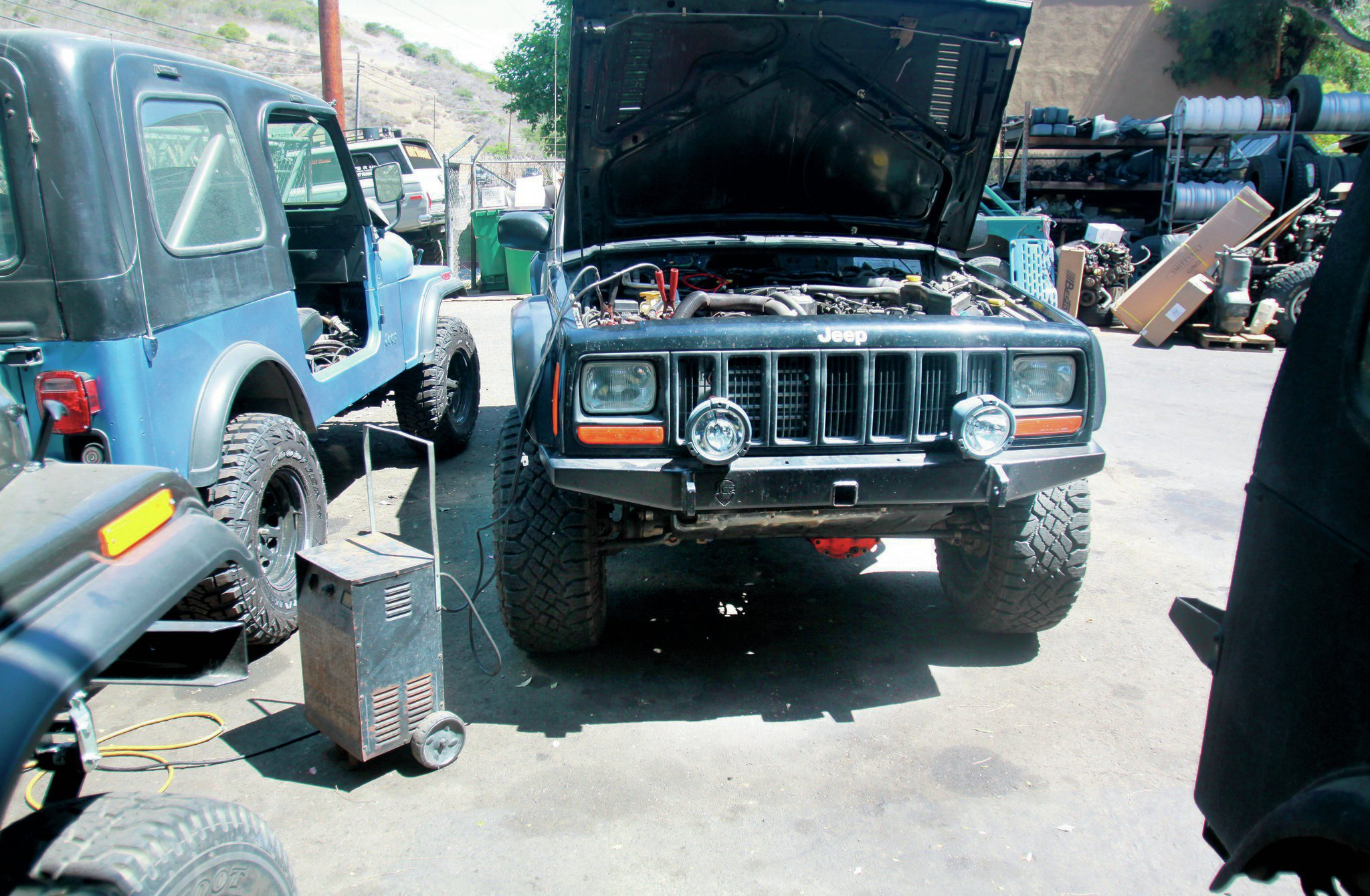 As it turns out, our nearly dead battery wasn't too happy being hooked up to the shop charger on the high amperage setting. We thought for sure the battery was dead, but we later tested it, and it came out just fine. Once it was charged, the tech decided just to try to swap coils again. The Jeep fired right up. It turns out we had not one, but two bad coils, both of which died from sitting and doing nothing. We still aren't sure how that is possible.